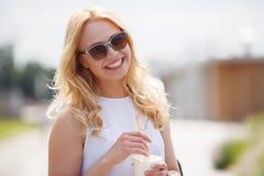 Smiling blonde drinking milkshake or smoothies in summer day Royalty Free Stock Photos