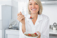 Smiling blonde eating cereal for breakfast Stock Images
