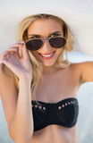 Smiling blonde in elegant black bikini looking over her sunglass Stock Image