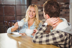 Smiling blonde enjoying coffee with friend Royalty Free Stock Photos