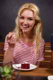 Smiling blonde enjoying a pastry Stock Photography