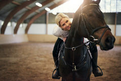Smiling blonde female leaning on black horseback. In indoor riding hall royalty free stock image