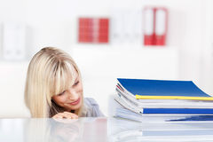 Smiling blonde female lookign at folders Stock Photos