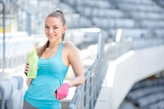 Smiling blonde fitness woman drinking water after complete outdoor workout. Smiling blonde fitness woman drinking water after complete hard outdoor workout royalty free stock images