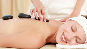 Smiling blonde getting hot stone massage stock footage
