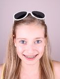 Smiling blonde girl with braces and sunglasses Royalty Free Stock Photography