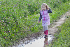 Smiling blonde girl with loose fair hair walking on dirt road rain puddle on purple clover flowers meadow Royalty Free Stock Images