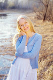 Smiling blonde girl outdoor in forest near river Royalty Free Stock Image
