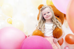 Smiling blonde girl playing with teddy bear Stock Photos