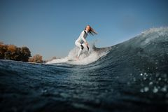 Smiling blonde girl riding on the wakeboard on the bending knees stock images