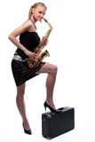 Smiling blonde girl with saxophone and suitcase Royalty Free Stock Photos