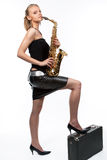 Smiling blonde girl with saxophone and suitcase Stock Photography