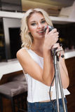 Smiling blonde girl singing with a microphone Royalty Free Stock Photography
