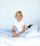 Smiling blonde girl sitting on a bed Stock Photography