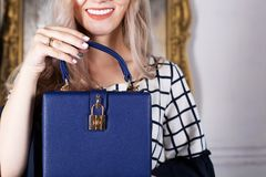 Smiling blonde girl in sunglasses holding blue leather purse. Em royalty free stock photography