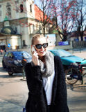 Smiling blonde girl talking by phone. Stock Photo