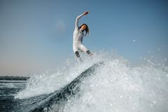 Smiling blonde girl jumping on the green wakeboard on the bending knees stock photo