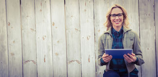Smiling blonde in glasses using tablet pc Royalty Free Stock Photo