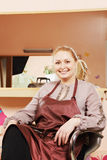 Smiling hairdresser in chair Royalty Free Stock Photos