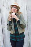 Smiling blonde in hat holding disposable cup Royalty Free Stock Photo