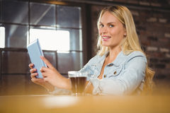 Smiling blonde having coffee and using tablet computer Royalty Free Stock Images