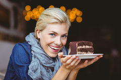 Smiling blonde holding a chocolate cake Stock Image