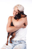 Smiling blonde holding a dog Stock Photography