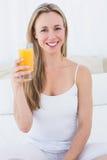 Smiling blonde holding glass of orange juice Stock Images