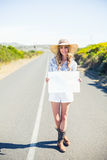 Smiling blonde holding sign while hitchhiking on the road. In summertime Royalty Free Stock Photos