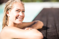 Smiling blonde leaning on pools edge Stock Photos