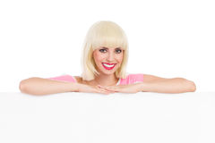Smiling blonde leaning on a white banner Royalty Free Stock Image