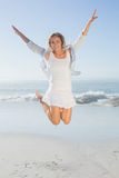 Smiling blonde leaping by the sea Stock Image