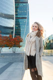 Smiling blonde in long coat standing on street in fall Stock Photos