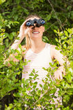 Smiling blonde looking through binoculars. In the nature Royalty Free Stock Images