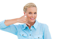 Smiling blonde looking at camera and doing a symbol of phone wit Royalty Free Stock Photography