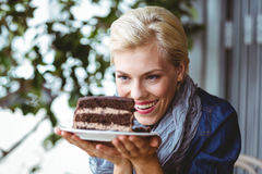 Smiling blonde looking a chocolate cake Royalty Free Stock Image