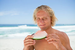 Smiling blonde man holding a piece of a watermelon Royalty Free Stock Photos