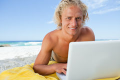 Smiling blonde man lying on the beach while using his laptop Royalty Free Stock Image