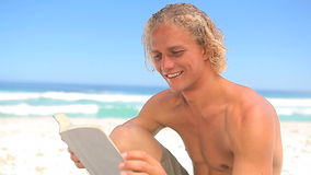 Smiling blonde man reading a novel. On the beach stock video