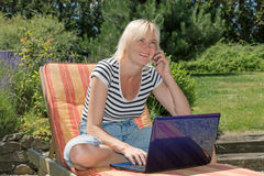 Smiling  blonde middle aged woman is calling outdoors Royalty Free Stock Image