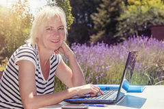 Smiling blonde middle aged woman outdoors Stock Photo