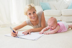 Smiling blonde mother with her baby girl writting on a copybook Stock Images
