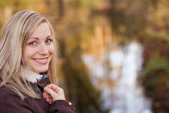 Smiling blonde (outdoor). Young blonde female smiling - nice colorful background Stock Images