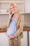Smiling blonde pregnancy phoning Stock Photography