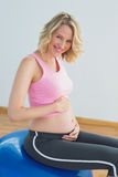 Smiling blonde pregnant woman touching belly on exercise ball stock photography