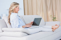 Smiling blonde relaxing on couch with her laptop Stock Photos