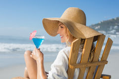 Smiling blonde relaxing in deck chair by the sea holding cocktail Royalty Free Stock Images