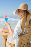 Smiling blonde relaxing in deck chair by the sea holding cocktail Stock Photos