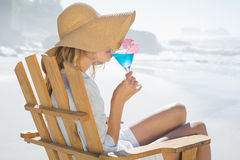 Smiling blonde relaxing in deck chair by the sea sipping cocktail Royalty Free Stock Photography