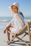 Smiling blonde relaxing in deck chair by the sea Stock Photos